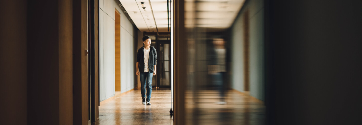 young man walking down a hallway