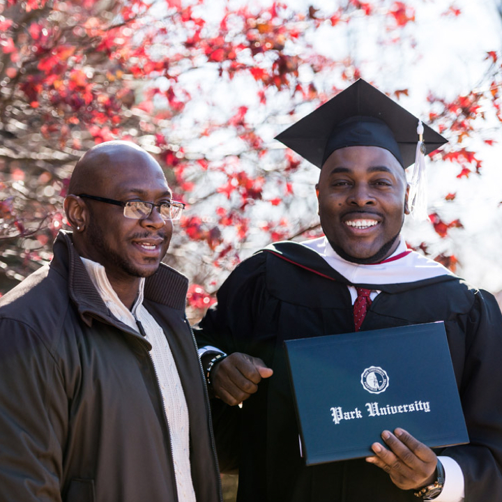 A Park graduate posing with his diploma