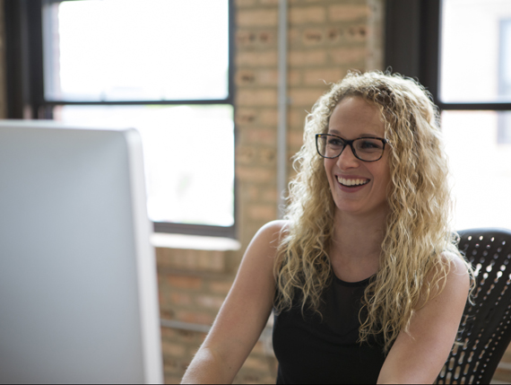 woman laughing and looking at computer