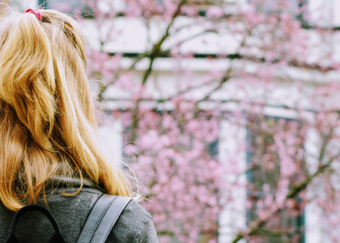 young woman wearing backpack facing cherry blossom trees outside