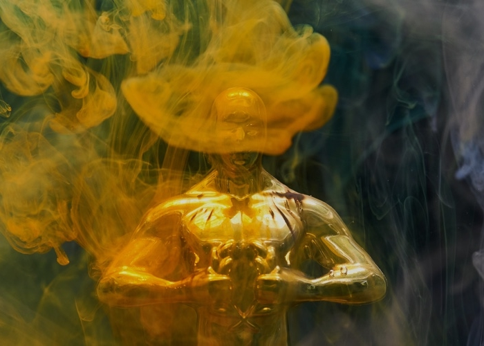 gold statue award surrounded by gold smoke