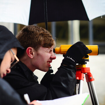 male student peering through a surveying instrument