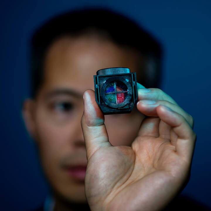a man who is out of focus holding a small colored cube that is in focus