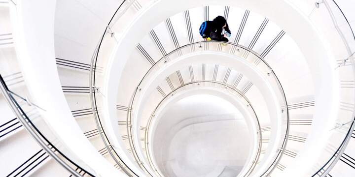 student ascending a white, spiral staircase