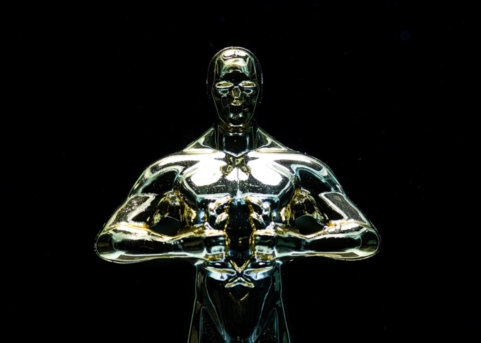 silver man statuette with a black background