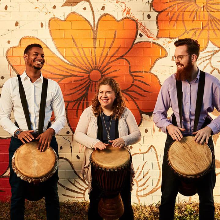 three people playing bongos