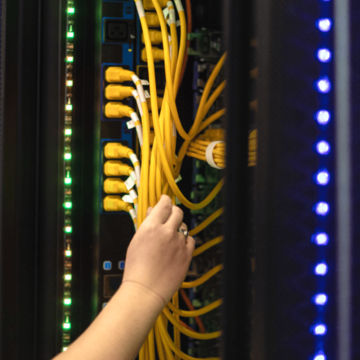 a person's hand holding cables connected to a server