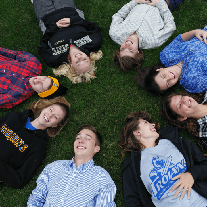 students laying on the grass with their heads in a circle