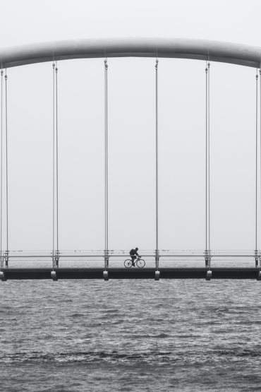 person riding a bike across a bridge over water