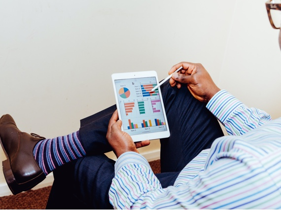 man holding a tablet and reviewing charts and graphs