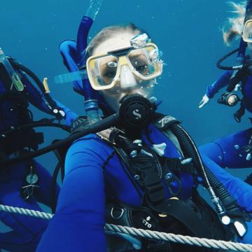 female student scuba diving underwater