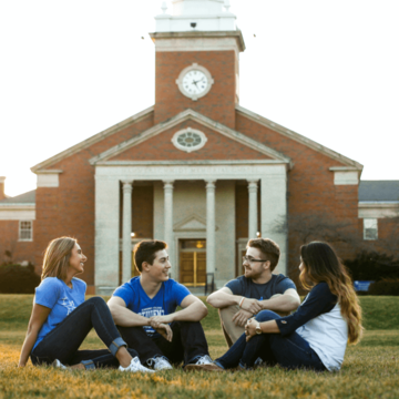 a group of students sitting outside of a clocktower