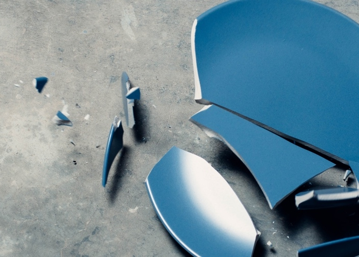 A blue dish plate falling and shattering on the ground