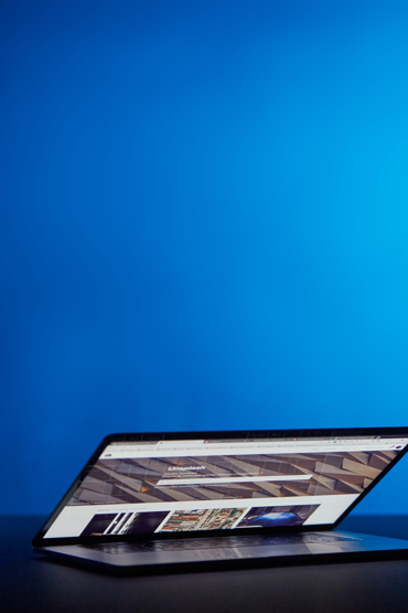 a half-open laptop against a blue background