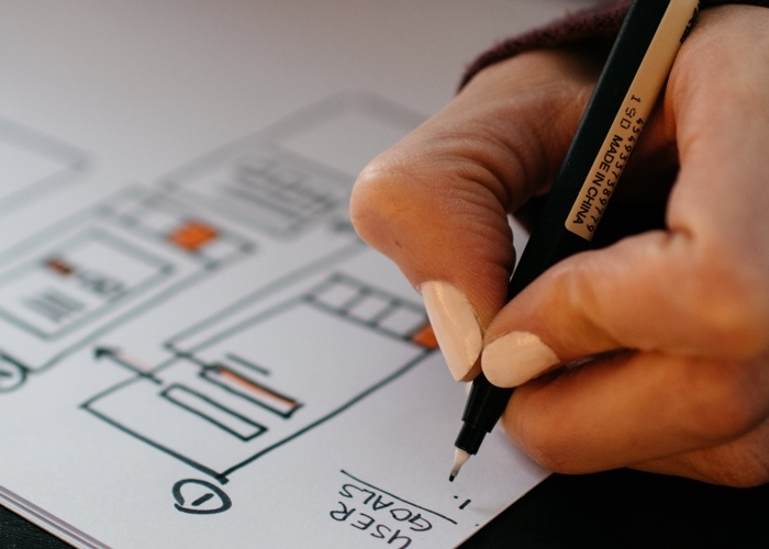person writing wireframes for higher ed website migration