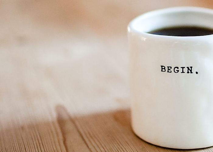 """coffee mug with the word """"begin"""" printed on the cup"""