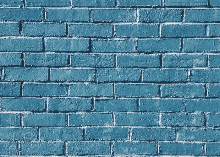 white brick wall with blue painted bricks