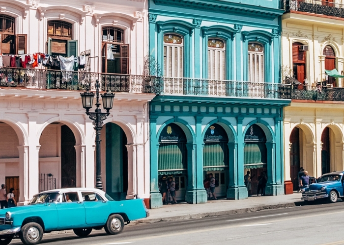 Pastel colored buildings lined along a Cuban street.
